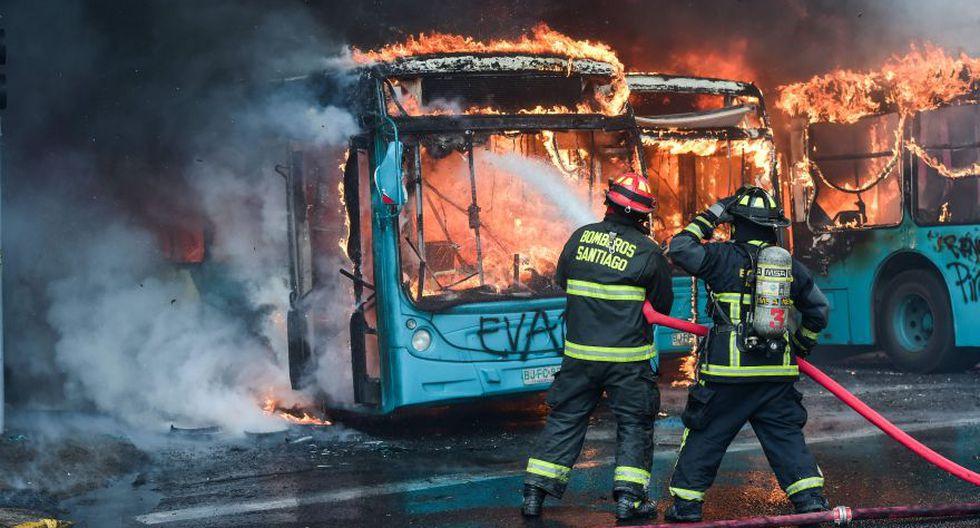 Los bomberos chilenos extinguen un autobús en llamas durante los enfrentamientos entre los manifestantes y la policía antidisturbios en Santiago. (Foto: AFP).