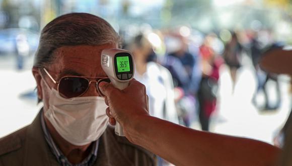 Un trabajador toma la temperatura de un hombre antes de ingresar al centro comercial (Foto: AP Photo/Esteban Felix)