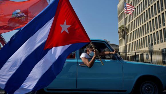 Cubanos pasan frente a la embajada de Estados Unidos durante un mitin para pedir el fin del bloqueo de Estados Unidos contra Cuba, en La Habana, 28 de marzo de 2021 (Foto: Yamil Lage / AFP)
