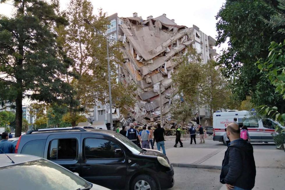 Los lugareños de Esmirna observan un edificio dañado después de que un fuerte terremoto azotó el mar Egeo el viernes y se sintió tanto en Grecia como en Turquía. (REUTERS/Tuncay Dersinlioglu).