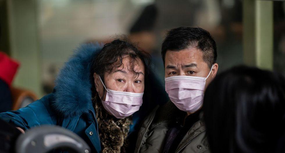 Las personas que viajan para el Año Nuevo Lunar usan máscaras protectoras mientras se dirigen al área de partida en el Aeropuerto Internacional Capital de Beijing (Foto: AFP)