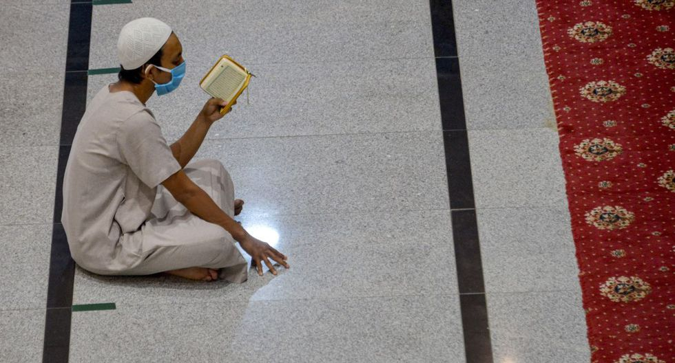 Un hombre con una máscara facial lee el Corán después de las oraciones del viernes durante el mes sagrado islámico del Ramadán en Indonesia. (CHAIDEER MAHYUDDIN / AFP).