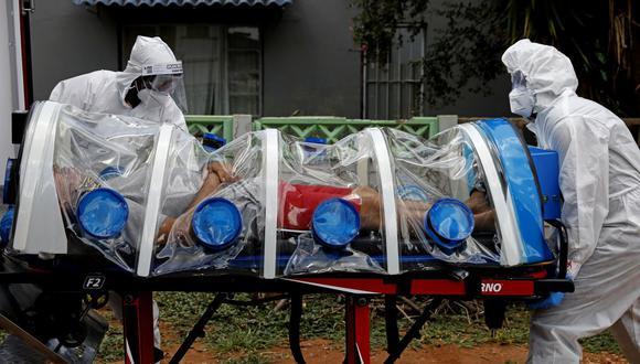 Los paramédicos de la Unidad Especial de Infecciones de la ciudad de Tshwane, Sudáfrica, trasladan a un hombre que muestra síntomas del coronavirus COVID-19. (Foto de Phill Magakoe / AFP).