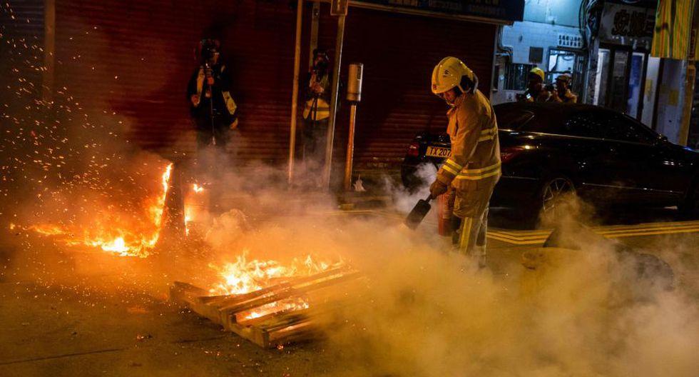 Un bombero apaga un fuego encendido por los manifestantes en el distrito Kowloon. (Foto: AFP).