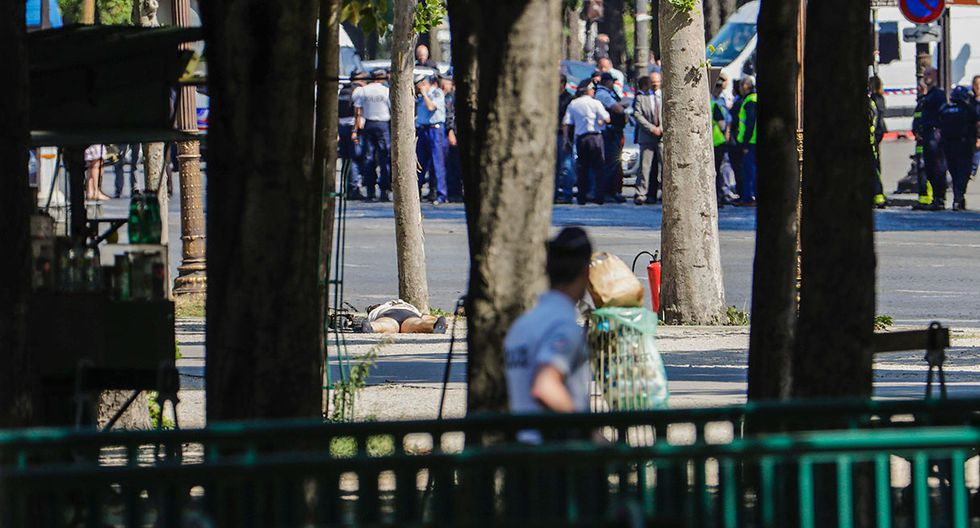 """A bomb-disposal remote controlled device (C-L) checks the body of a man (C) lying in a sealed off area, with police officers in the background, on June 19, 2017 on the Champs-Elysees avenue in Paris, after a car crashed into a police van before bursting into flames, with the driver being armed, probe sources said. A source close to the investigation said the driver was """"seriously injured"""".  / AFP / Thomas SAMSON"""