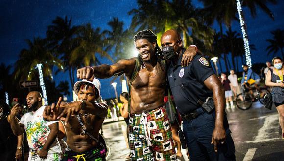 La policía de Miami Beach, Florida, escolta a las personas fuera de Ocean Drive mientras el toque de queda está en efecto el 27 de marzo de 2021, en medio de la pandemia de coronavirus. (Foto de CHANDAN KHANNA / AFP).