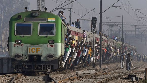 Los pasajeros se cuelgan de un tren cuando parte de una estación en las afueras de Nueva Delhi, India. (Foto: Prakash SINGH / AFP).