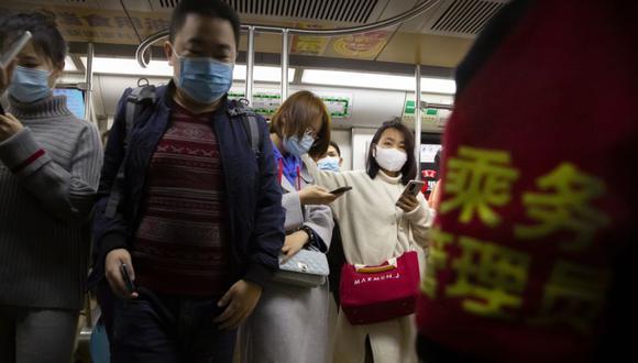 Personas que usan mascarillas para protegerse contra el coronavirus viajan en un tren subterráneo en Beijing. (Foto: AP / Mark Schiefelbein).