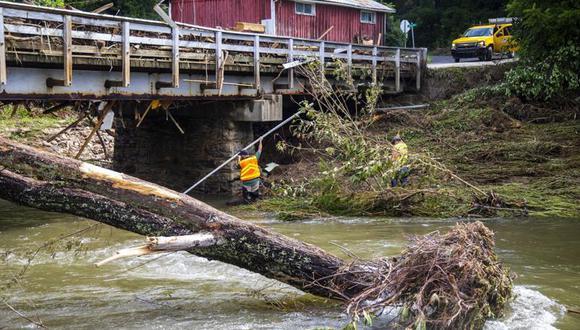 Trabajadores del Departamento de Transporte de Carolina del Norte evalúan los daños de un puente sobre el Río Pigeon, el jueves 19 de agosto de 2021, en Bethel, Carolina del Norte, a raíz de las inundaciones causadas por la tormenta tropical Fred. (Travis Long/The News & Observer vía AP).