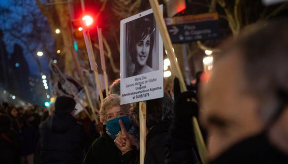 Manifestantes que llevan retratos de personas desaparecidas durante la dictadura militar (1973-1985) participan en una protesta convocada por la organización Madres y Familiares de Desaparecidos, en Montevideo el 4 de septiembre de 2020. (PABLO PORCIUNCULA / AFP).