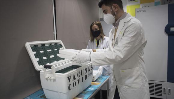 Imagen referencial. Técnico de laboratorio abre una nevera portátil con vacunas Pfizer-BioNTech contra el coronavirus en la cooperativa de distribución mayorista Bidafarma en Santa Fe, en las afueras de Granada, el 21 de enero de 2021. (JORGE GUERRERO / AFP).
