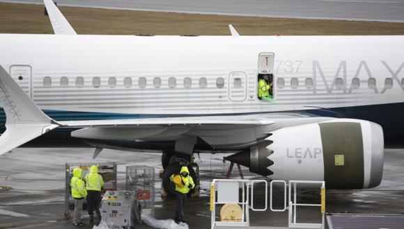 Trabajadores son fotografiados junto a un avión Boeing 737 MAX 9 en la pista de la fábrica Boeing Renton. (Foto: AFP)