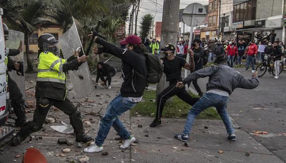 Manifestantes chocan con la policía antidisturbios durante una protesta contra la muerte del abogado Javier Ordóñez, quien falleció a manos de las fuerzas del orden colombiana. (Foto de Juan BARRETO / AFP).