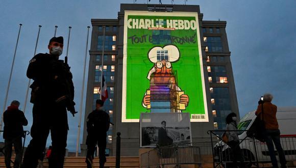 La policía monta guardia mientras las caricaturas del semanario satírico francés Charlie Hebdo se proyectan en la fachada del Hotel de Region en Montpellier, el 21 de octubre de 2020, durante un homenaje nacional al profesor de francés Samuel Paty. (Foto de Pascal GUYOT / AFP).