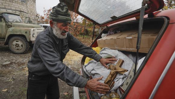 El armenio Nikolai Karapetyan coloca su crucifijo en el carro que lleva sus pertenencias, mientras prepara su salida de Maraga, en Nagorno Karabaj. Como parte del acuerdo, miles de armenios de la región deberán marcharse. AP