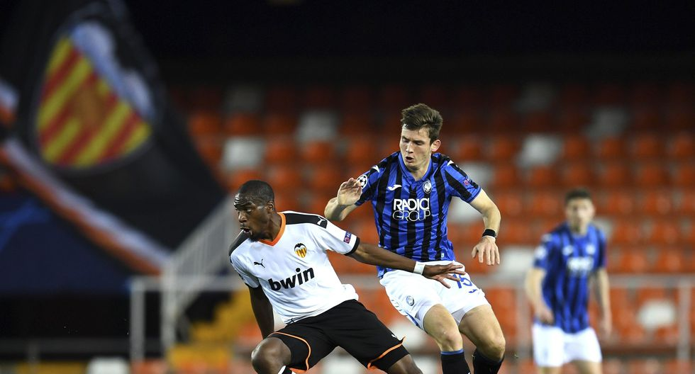 Valencia's Geoffrey Kondogbia, left, duels for the ball with Atalanta's Marten de Roon during the Champions League round of 16 second leg soccer match between Valencia and Atalanta in Valencia, Spain, Tuesday March 10, 2020. The match is being in an empty stadium because of the coronavirus outbreak. (UEFA via AP)