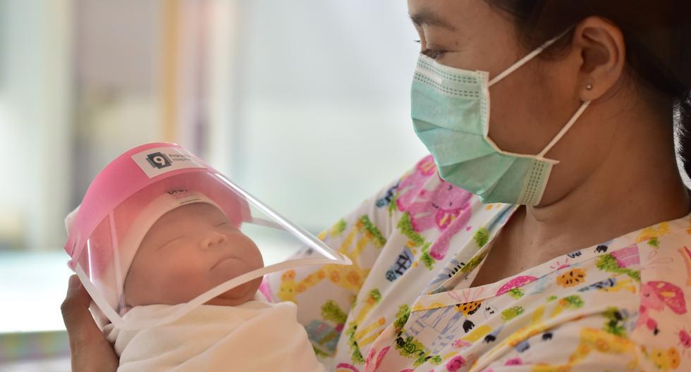 Imagen referencial muestra a una enfermera sosteniendo a un bebe recién nacido con un protector facial en un hospital de un país de Asia. (Lillian SUWANRUMPHA / AFP).