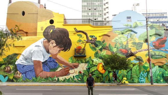 Los limeños que transitan por la cuadra 6 de Arenales pueden apreciar el grafiti de una niña gigante y curiosa, inmersa en una naturaleza de fábula que la inspira a dibujar. Abajo posa el autor piurano. (FOTO: CCE)