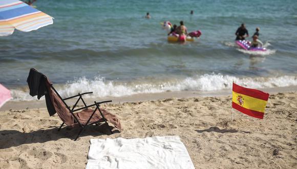Unas personas disfrutan de la playa en Palma de Mallorca, España, el domingo 26 de julio de 2020, en medio del rebrote del coronavirus. (AP Foto/Joan Mateu).