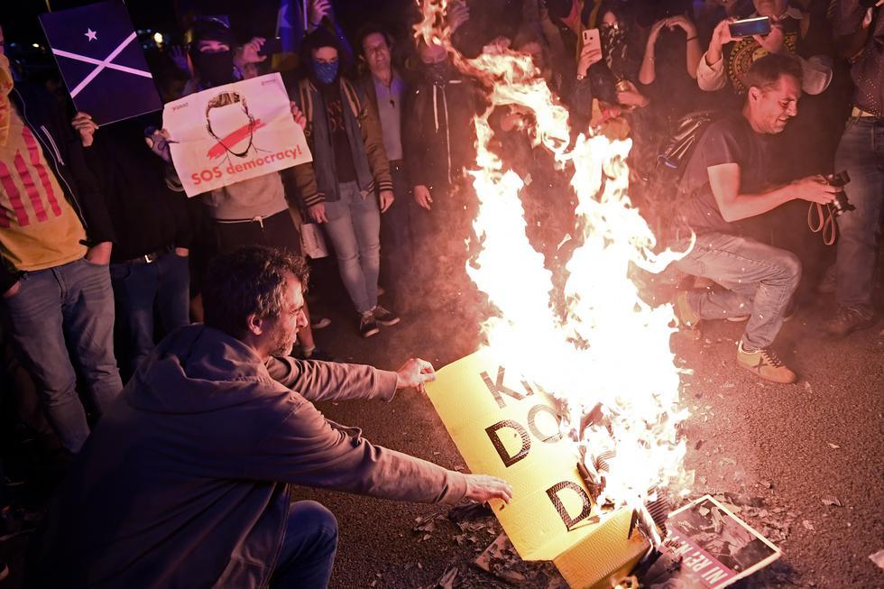 """Los manifestantes independentistas queman fotos y carteles contra la monarquía española durante una protesta llamada """"ni Rey ni miedo"""" contra la visita de la familia real española en Barcelona. (Foto: AFP)"""