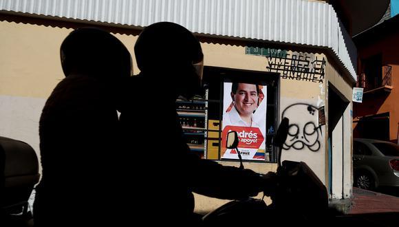 Dos personas cruzan en moto frente a un cartel del candidato Andrés Arauz. EFE