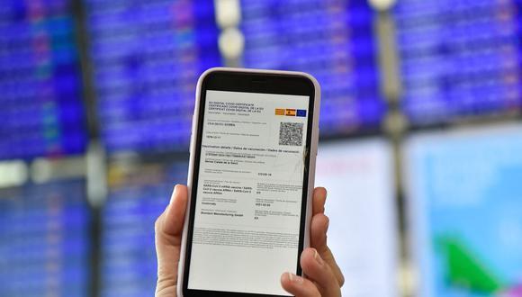 Una mujer muestra su certificado Covid Digital de la Unión Europea en su teléfono móvil en el aeropuerto de El Prat en Barcelona el 1 de julio de 2021. (Foto de Pau BARRENA / AFP).