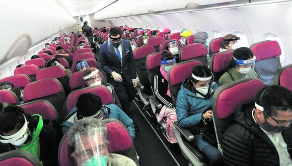 Los pasajeros del avión mantienen puestas sus mascarillas y caretas, previo a que el avión parta desde Lima con destino a Cusco. (Foto: Renzo Salazar)