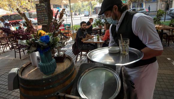 Un mesero atiende a un grupo de personas mientras disfrutan de un almuerzo en una terraza en Santiago de Chile tras el fin de la cuarentena por coronavirus. (EFE/Alberto Valdés).