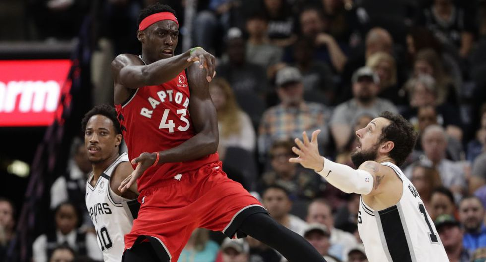 Toronto Raptors forward Pascal Siakam (43) passes the ball over San Antonio Spurs guard Marco Belinelli (18) during the second half of an NBA basketball game in San Antonio, Sunday, Jan. 26, 2020. (AP Photo/Eric Gay)