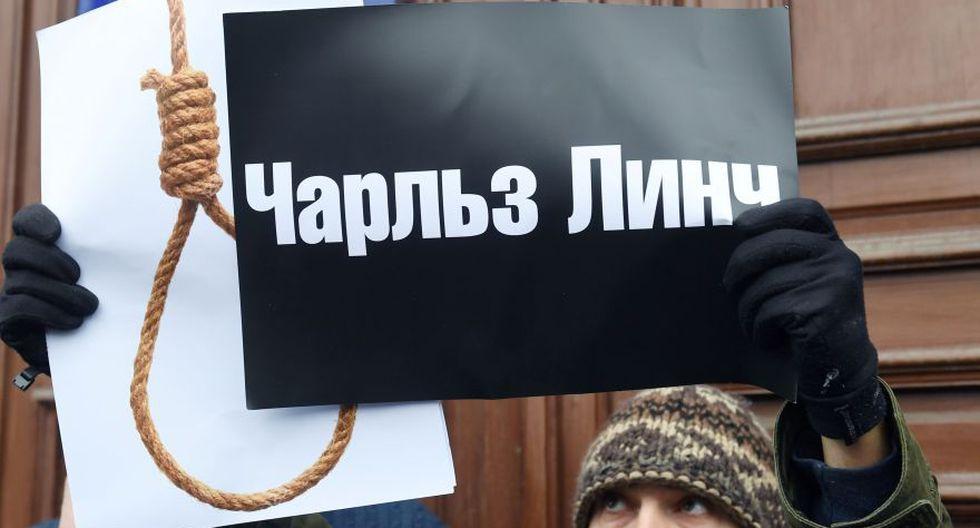 """Condenado a siete años de cárcel en junio, Rososhansky, sobrino de un juez, tenía muchas posibilidades de ser amnistiado y puesto en libertad, hasta que la corte de apelación de Kiev rechazó su recurso el pasado miércoles. En el cartel se lee """"Charles Lynch"""", que connota linchamiento. (Foto: AFP)"""