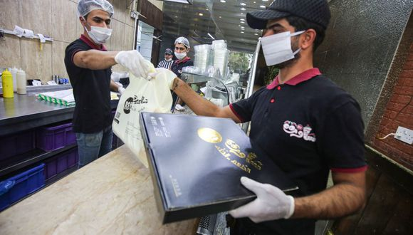 Los clientes también deberán tener equipos de protección para ser atendidos. (Foto de AHMAD AL-RUBAYE / AFP)