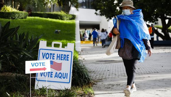"""Una mujer pasa junto a un cartel de """"Vote aquí"""" en el Ayuntamiento de Miami Beach, Florida, el 19 de octubre de 2020. (Foto de Eva Marie UZCATEGUI / AFP)."""