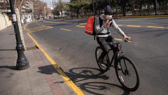 Un repartidor de una aplicación móvil es visto este jueves en una calle semivacía del centro de Santiago de Chile, durante la cuarentena obligatoria decretada para frenar el avance del coronavirus COVID-19. (EFE/Alberto Valdes).