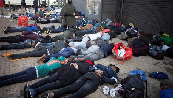Los saqueadores detenidos permanecen en el suelo tras ser detenidos por la policía en Johannesburgo, Sudáfrica, el 13 de julio de 2021. (EFE / EPA / KIM LUDBROOK).