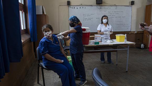 Una maestra recibe la primera dosis de la vacuna CoronaVac para el coronavirus COVID-19, de la china Sinovac Biotech, en la escuela pública Salvador Sanfuentes, en Chile. (AP Foto/Esteban Félix).