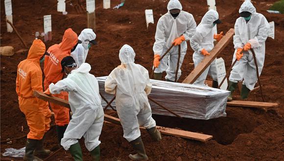 Trabajadores entierran a una víctima de coronavirus en un cementerio de Yakarta, Indonesia. (AFP / Bay ISMOYO).