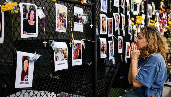 Una mujer reza frente a las fotos en el memorial improvisado para las víctimas del derrumbe del edificio, cerca del lugar del accidente en Surfside, Florida, al norte de Miami Beach. (CHANDAN KHANNA / AFP).