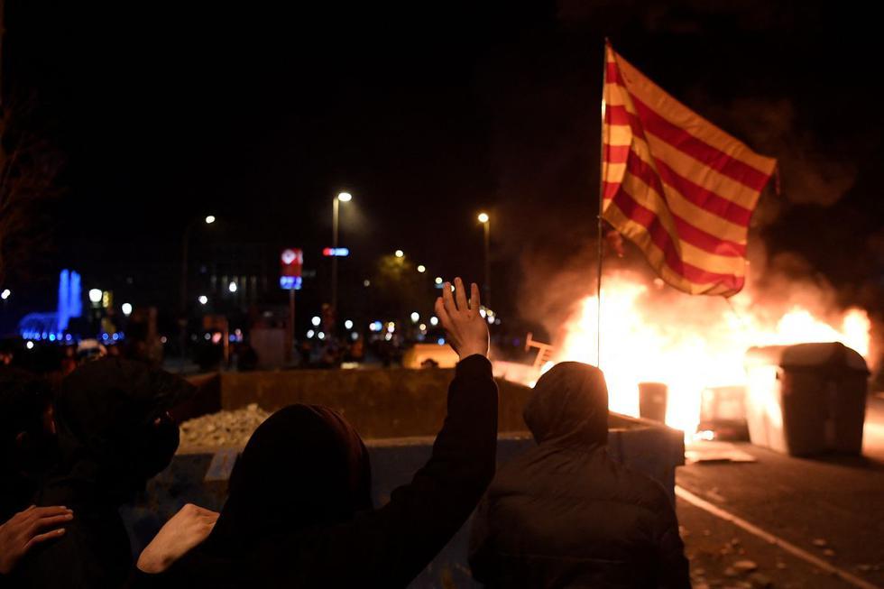 Los manifestantes se refugian detrás de un contenedor de basura durante los enfrentamientos con las fuerzas policiales regionales catalanas Mossos d'Esquadra. (Foto de Josep LAGO / AFP).