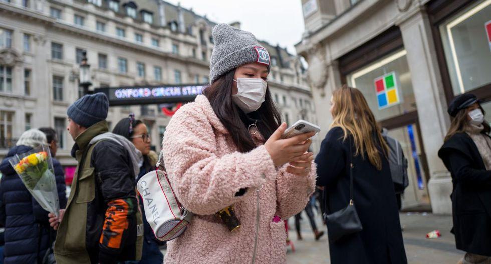 Una mujer con una máscara protectora camina por la carretera en Oxford Circus, en el centro de Londres, Reino Unido, país que es criticado por no tomar medidas fuertes para contener el coronavirus. (Foto: AFP).
