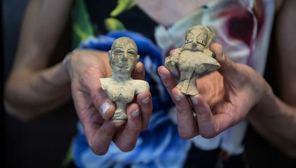Una funcionaria de aduanas francesa muestra unas piezas arqueológicas requisadas y devueltas a la Embajada de Pakistán, el pasado 24 de junio en el aeropuerto de Roissy-Charles de Gaulle, cerca de París. (Foto: AFP)