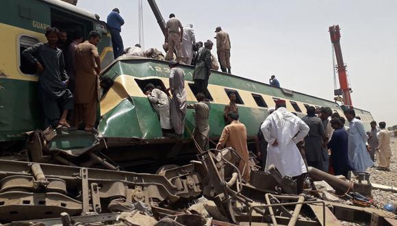Personal de seguridad y los ciudadanos se acercan al lugar del accidente de tren en el área de Daharki, en la provincia norteña de Sindh, Pakistán. (Foto de Shahid ALI / AFP).