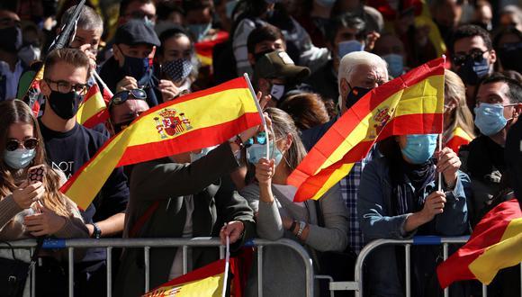 Banderas de España ondean entre los asistentes al acto organizado con motivo del Día de la Fiesta Nacional, en Madrid este lunes. (Foto: EFE)