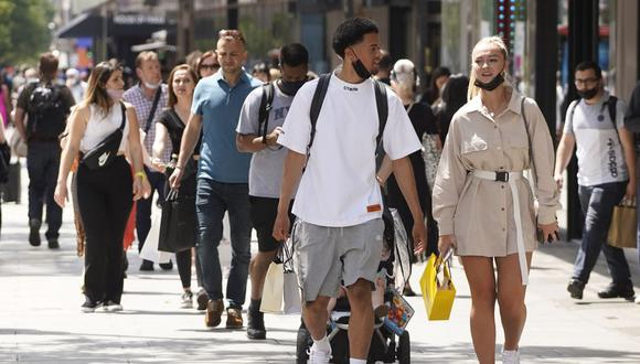 Los peatones, algunos con cubiertas faciales debido al coronavirus, pasan frente a las tiendas de Oxford Street en el centro de Londres, Reino Unido, el 7 de junio de 2021. (Niklas HALLE'N / AFP).