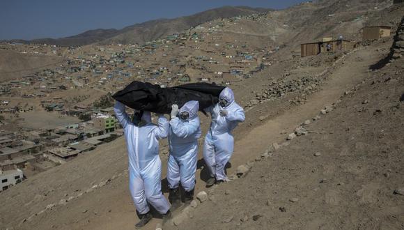 Los venezolanos Luis Zerpa, Luis Brito y Jhoan Faneite cargan con una bolsa con el cadáver de Marcos Espinoza, de 51 años y que se cree que murió por coronavirus cerca de Pachacamac, en las afueras de Lima, Perú. (AP Foto/Rodrigo Abd).