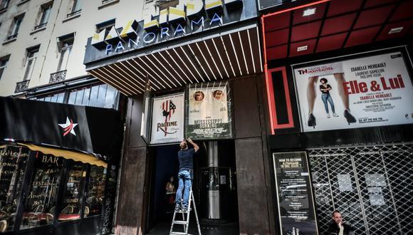 Imagen referencial. Un empleado retira carteles de películas fuera del Teatro Cine Max Linder en París. (STEPHANE DE SAKUTIN / AFP).
