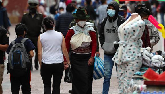 Varias personas caminan frente a comercios informales en las calles de Quito (Ecuador). (Foto: EFE/ José Jácome/Archivo).