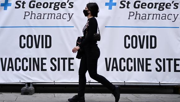 Una persona camina al frente de un centro de vacunación contra el coronavirus, en Londres. EFE