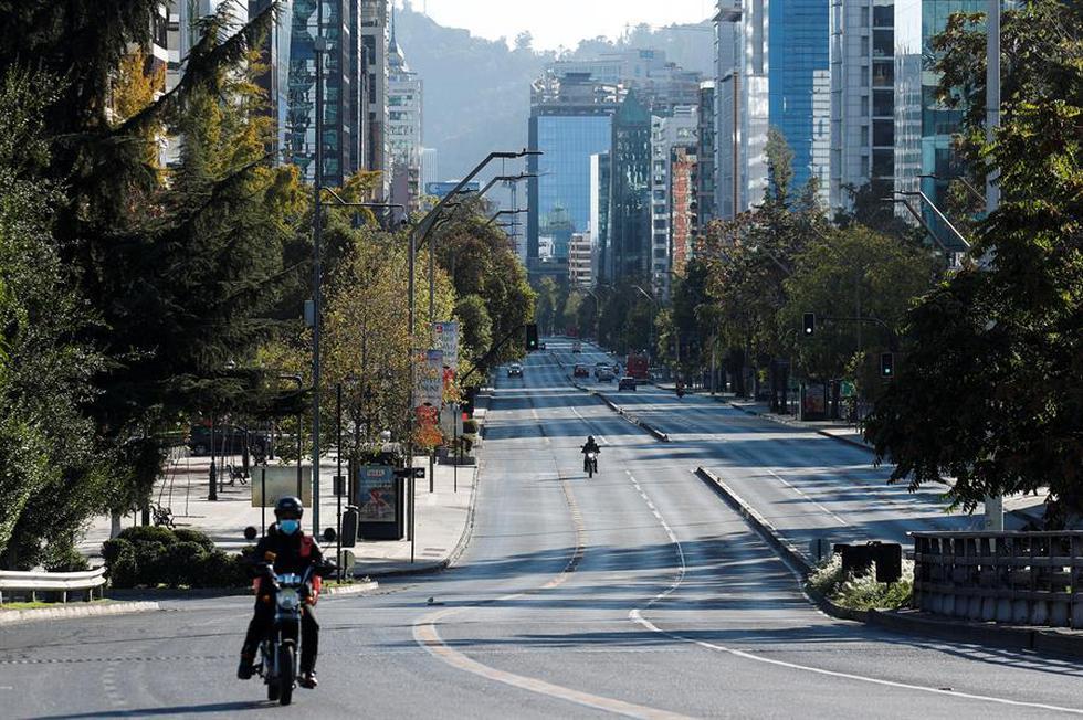 Dos motociclistas transitan por una avenida casi vacía durante la cuarentena obligatoria decretada en prácticamente todo Chile ante el avance de la pandemia de coronavirus covid-19. (Foto: EFE/Alberto Valdés).