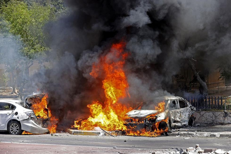 Carros en llamas después de que un cohete lanzado desde la Franja de Gaza impactara contra ellos en la ciudad de Ashkelon. (Foto de JACK GUEZ / AFP).
