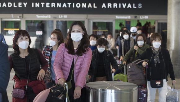 Los pasajeros usan máscaras protectoras para protegerse contra la propagación del Coronavirus cuando llegan en un vuelo desde Asia al Aeropuerto Internacional de Los Ángeles, California. (Foto: AFP).